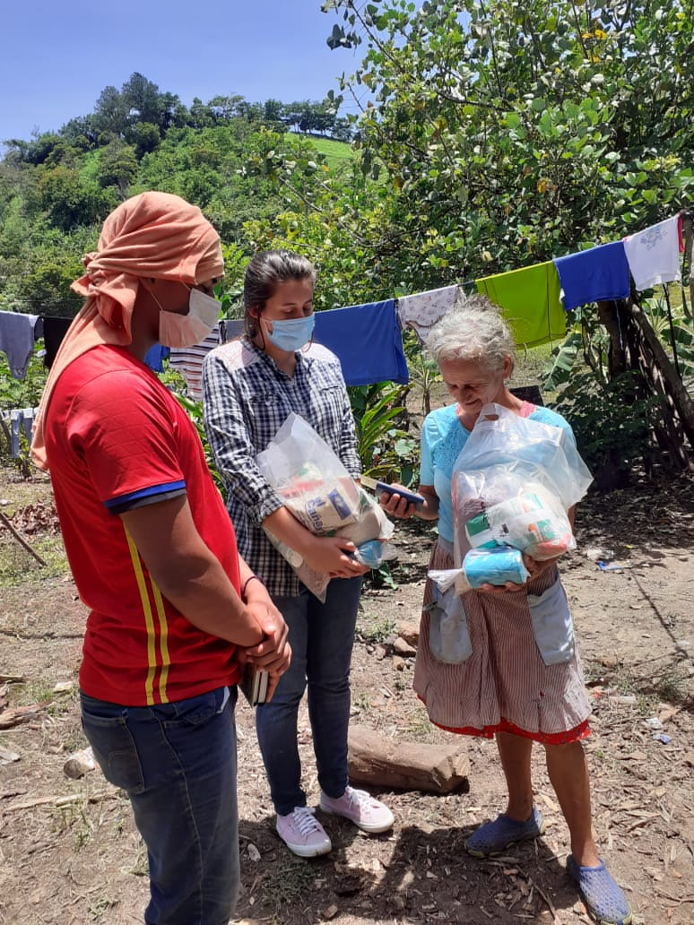Students Josue & Cecilia Pray as they give food to a lady